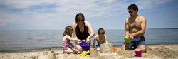 Family In Bathing Suits Making Sand Castles Grand