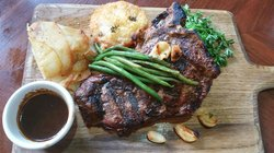 T-Bone steak served with au gratin potatoes, seasonal vegetables and a grilled herb and parmesan tomato