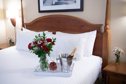 Roses And Champagne On Bed